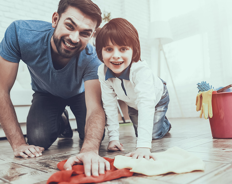 Dad and son smiling cleaning the floor